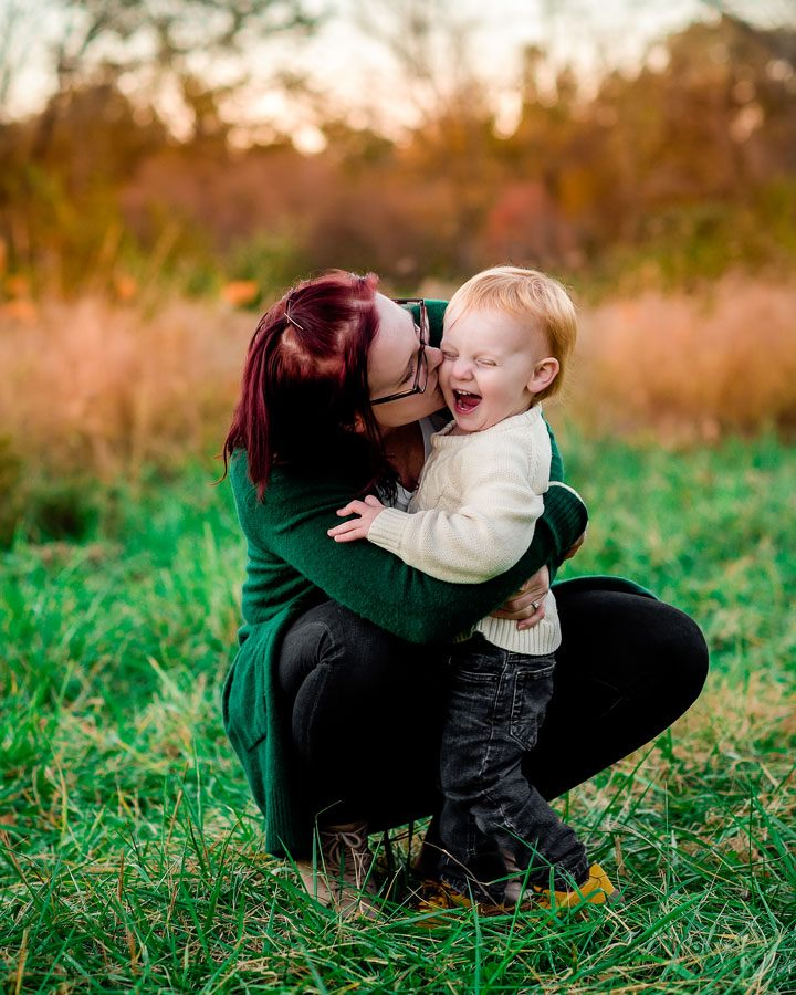Mother and baby giving love while posing for family photos